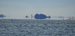 Saari ja sen heijastus vedessä.